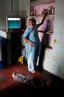 Nafeesa, 27, tends to her 4 children in her house in a slum in Tonk, Rajasthan, India, on 19th June 2012. Nafeesa's health deteriorated from bad birth spacing and over-working. While her husband works far from home, she rolls bidis (indian cigarettes) to make an income and support the family. She single-handedly runs the household and this has taken a toll on her health and financial insufficiencies has affected her children's health. Photo by Suzanne Lee for Save The Children UK