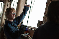 Katrin Iken, a scientist from the University of Alaska Fairbanks, shows how thick she thinks the ice is based on the broken chunks she can see sliding past the sides of the ship. She helps the Coast Guard decide which patch of ice is safe enough to hold a dozen or so people and their equipment.