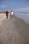 Couple walking on the sandy beach afternoon sand shells Folly Beach South Carolina