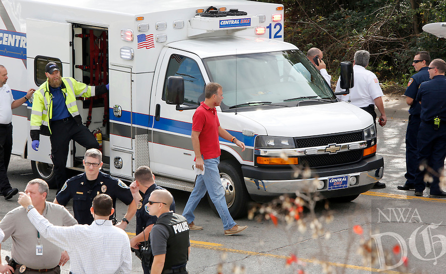 NWA Democrat-Gazette/DAVID GOTTSCHALK  A man (top center) exits an ambulance before inspecting the hood of a small plane as emergency responders secure the scene of a small airplane crash Tuesday, November 3, 2015, on Martin Luther King Boulevard in Fayetteville. Bill Simon, 56, Cliff Slincard, 59, and Maurice Willis, 47, were on the plane that deployed an emergency parachute attached to plane after an attempt at making an emergency landing at Drake Field in Fayetteville. The plane took off from Bentonville airport. All three men were transported to area hospitals with non life threatening injuries.