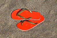 Pair Of Red Flip Flops Sandals On Black Sand Beach