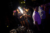 A young woman finishes her glass of champagne and an attendant lights up a flare while opening another bottle of champagne in The club LAP located in Hotel Samrat in New Delhi, India. Photograph: Sanjit Das/Panos