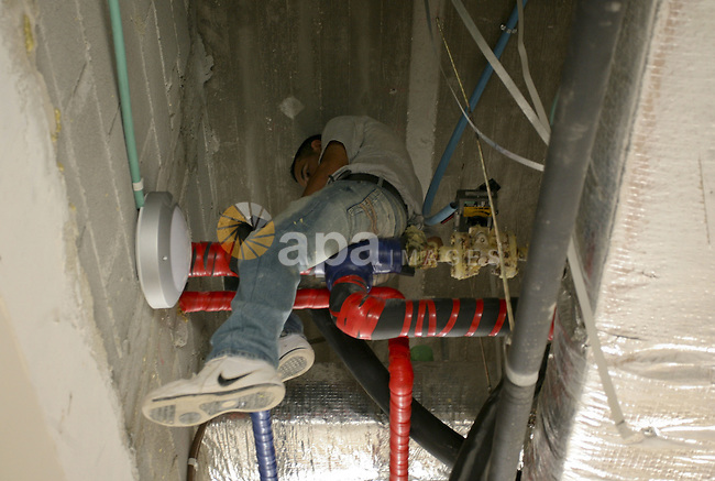 A Palestinian worker repairs pipelines ,near West Bank city of Jericho , on Oct. 10.2010 . Jericho is one of the oldest continuously inhabited cities in the world, with evidence of settlement dating back to 9000 BC,it has a population of over 20,000 Palestinians. Situated well below sea level on an east-west route 16 kilometres (10 mi) north of the Dead Sea, Jericho is the lowest permanently inhabited site on earth. Photo by Eyad Jadallah
