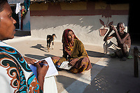 Shanti Adivasi (in white saree), 52, interviews Siya Saran (right) and Bacchi Saran (center), heads of a family of illiterate tribal villagers in their housing compound in Manikpur, Chitrakoot, Uttar Pradesh, India on 4th December 2012. Shanti used to be a wood gatherer, working with her parents since she was 3, and later carrying up to 100 kg of wood walking 12km from the dry jungle hills to her home to repack the wood which sold for 3 rupees per kg. After learning to read and write in an 8 month welfare course, at age 32, she became a reporter, joining Khabar Lahariya newspaper since its establishment in 2002, and making about 9000 rupees per month, supporting her family of 14 as the sole breadwinner. Photo by Suzanne Lee for Marie Claire France.