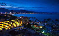 Fine Art Photograph. Night scene of Puerto Vallarta with its city lights surrounding Banderas Bay In the state of Jalisco Mexico. The glowing city lights of Puerto Vallarta, the blue pastel shades of the mountains, and the palm trees  reveal the beauty of this charming Pacific ocean scene.