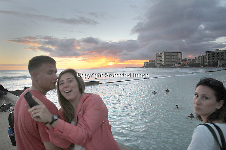"A young couple attempt to do a ""selfy""photograph at the the ""Wall"" at Waikiki."