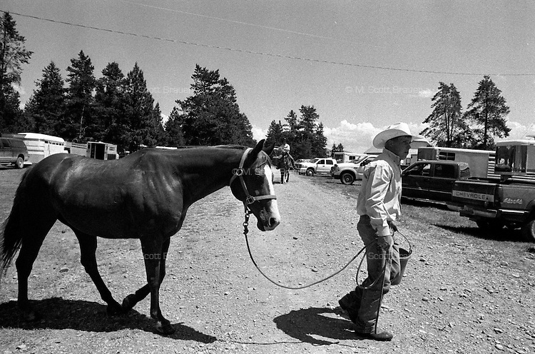 A man walks a horse on the rodeo grounds at the annual Lincoln Rodeo in Lincoln, MT in June 2006.  The Lincoln Rodeo is an open rodeo, which means competitors need not be a member of a professional rodeo association.