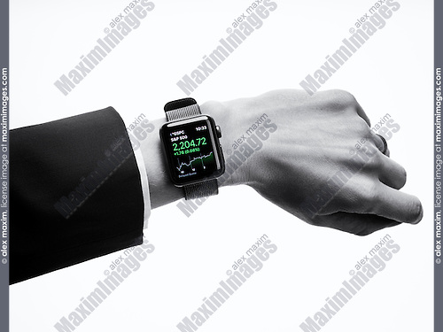 Woman wearing Apple Watch series 2 smartwatch on her wrist displaying stock market app, closeup of hand isolated on white background in black and white
