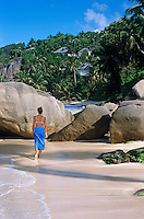A girl walks along the edge of the beautiful Anse Intendance beach on Mahe Island with the cottages of the Banyan Tree resort grouped along the shoreline
