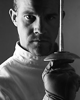 Man in fencing attire, staring, with foil poised vertically.
