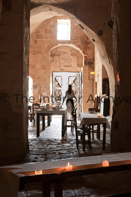 The dining room is housed in a former church at the unique Albergo Diffuso Le Grotte della Civita in Southern Italy