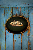On the living room wall a little model boat is held in place by two pins and simply framed within a section of old weatherboard