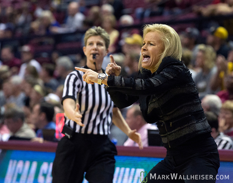 The referee tries to guide Florida State head coach Sue Semrau back as she signals her team during the first half of a second-round game of the NCAA women's college basketball tournament against Missouri in Tallahassee, Fla., Sunday, March 19, 2017. (AP Photo/Mark Wallheiser)