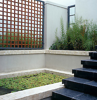 Inner japanese-style courtyard entrance enclosed by a wooden trellis with pond and black slate steps