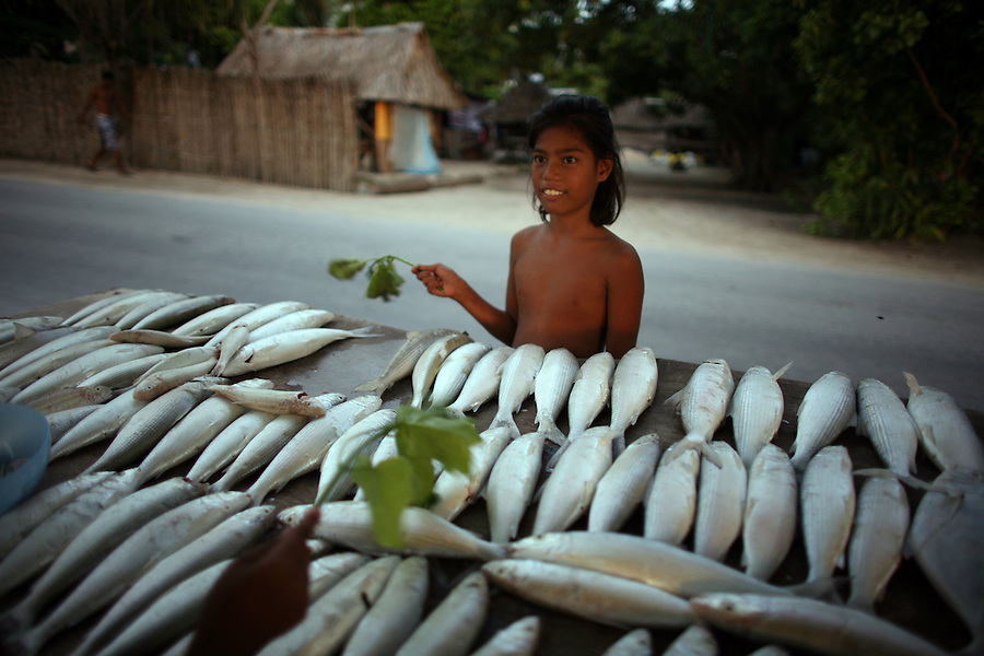 A young girl sells milk fish caught by her father, on the roadside in Tarawa. Young girls and women in Kiribati are under threat from foreign fishermen, who come to their country and have been reported to take young girls on to their boats to serve as sex workers.