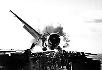 Crash landing of F6F on flight deck of USS ENTERPRISE while enroute to attack Makin Island.  Lt. Walter Chewning, catapult officer, clambering up the side of the plane to assist pilot, Ens. Byron Johnson, from the flaming cockpit.  November 1943.  (Navy)<br /> Exact Date Shot Unknown<br /> NARA FILE #:  080-G-205473<br /> WAR &amp; CONFLICT BOOK #:  964