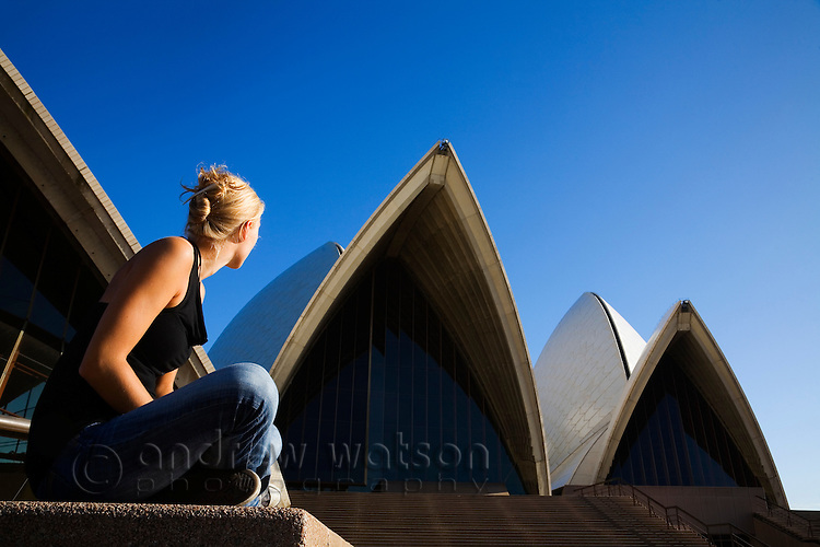 A woman looks up to the iconic roofs of the Sydney Opera House.  Sydney, New South Wales, AUSTRALIA.
