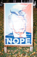 "Flanked by Clinton/Kaine campaign signs, a sign reading ""Nope"" and featuring a funny picture of Republican presidential nominee Donald Trump in the style of the Obama Hope poster from the 2008 campaign stands in a yard in Lexington, Massachusetts, USA, on Sun., Nov. 6, 2016."