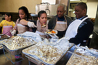 Volunteers from the United Palace Cathedral in the primarily Dominican Washington Heights in New York serve Thanksgiving Dinner to neighborhood residents and visitors on Thursday, November 22, 2012. The church expects to serve several hundred dinners giving diners a choice of turkey or chicken with an assortment of sides including mac n' cheese, plantains and collard greens.  (© Richard B. Levine)
