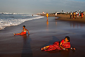 A fully clothed woman and a young boy are seen waiting for the big waves on Puri Beach along the Bay of Bengal in Puri, Orissa, India. A dip in its salty waters is believed to hold great religious significance, as a result these golden sand beaches sees is a never-ending rush of pilgrims and tourists. Photo: Sanjit Das/Panos