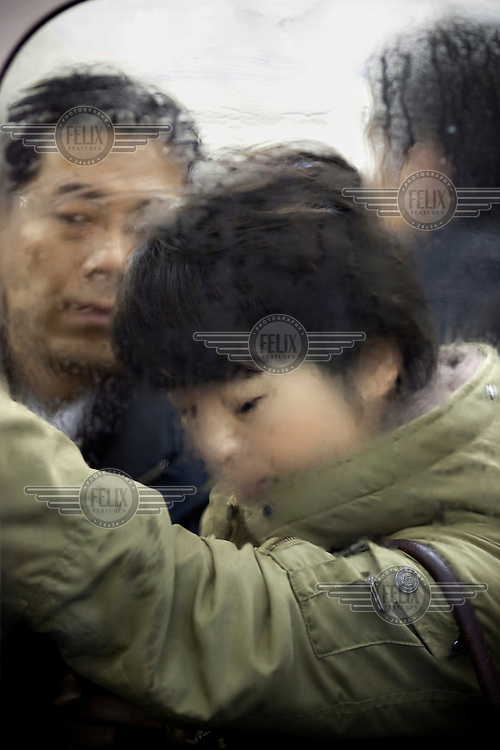 Commuters crammed into one of the train carriages at Shibuya station during morning rush hour.