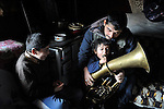 """THIS PHOTO IS AVAILABLE AS A PRINT OR FOR PERSONAL USE. CLICK ON """"ADD TO CART"""" TO SEE PRICING OPTIONS.   Milan Pesic gets help from one of his children as he practices his french horn inside his home in a Roma settlement in Belgrade, Serbia. He plays in a Roma band. The families that live here, many of whom survive from recycling cardboard and other materials, are under constant threat of eviction in order to make way for new high-rise office buildings."""