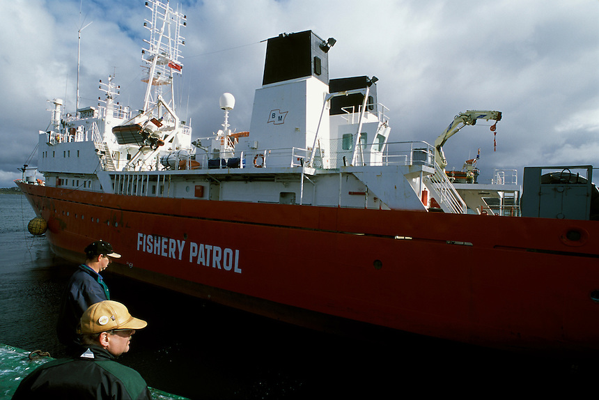 Capt. Trevor Betts, foreground, watches as the Dorada, one of two patrol vessels leased by the Falkland Islands Fishery Patrol, leaves port for a cruise in the Falkland Islands Conservation Zone. Created in 1986, the zone covers 34,000 square<br /> kilometers in a 320-kilometer radius around the islands. It is noted for its stocks of illex squid, cod and hake. Falkland officials are serious about defending the zone. In 2000, Betts and the Dorada fired on a Taiwanese squid jigger poaching inside the boundary, eventually bringing the ship in to face fines and legal charges.