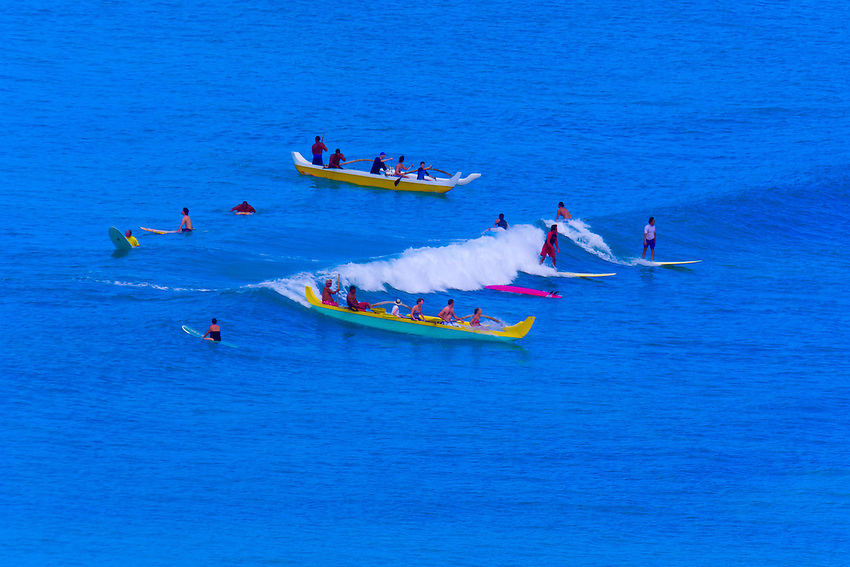 Surfers and outrigger canoes in the waters off Waikiki Beach, Honolulu, Oahu, Hawaii, USA