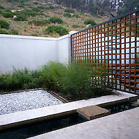 Inner japanese_style courtyard with tiny rill adjacent to the entrance hidden by wooden trellis