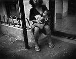 Homeless woman breat-feeds baby and begs for change outside exit for McDonald's fast food restaurant, Ermita, Manila, Philippines.