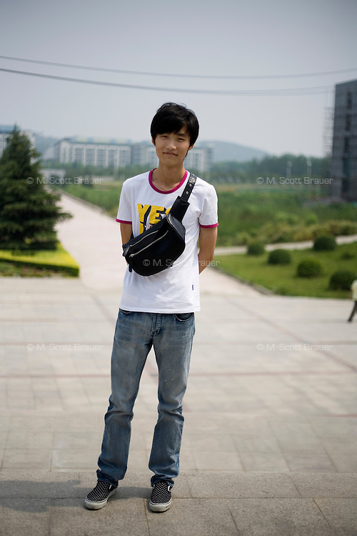 Honghun, a student, age 24, poses for a portrait in Nanjing. Response to 'What does China mean to you?': 'A country'  Response to 'What is your role in China's future?': 'Central.' [said jokingly]