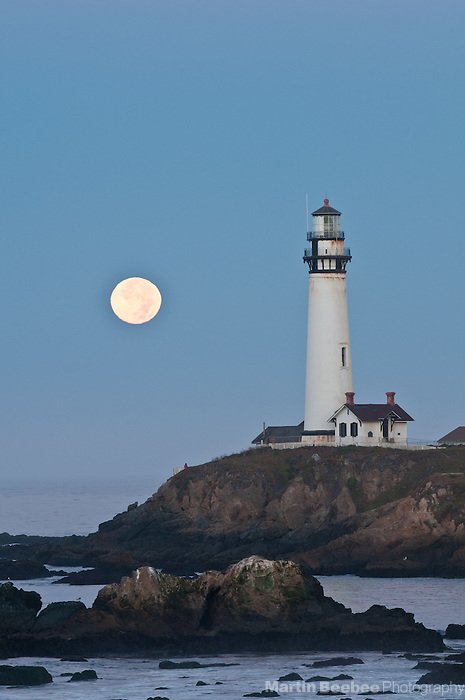 Full moon setting behind Pigeon Point Lighthouse, California