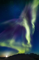 Aurora borealis streak heavenward over the Chandalar shelf, Brooks mountain range, Arctic Alaska, moon rises in the distance on the vernal equinox, March 21st, 2003 at 1:00 a.m.