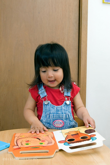 Berkeley CA Girl, Guatemalan, two-years-old, pointing out and naming animals in book  MR