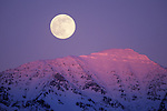 The full moon rises above the Swan Range of mountains in western Montana near Condon
