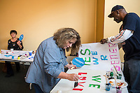 Campaign volunteers paint signs for a rally as Vice President Joe Biden greets staff during an unscheduled stop at a campaign field office while on a two-day campaign swing through Iowa on Monday, September 17, 2012 in Ottumwa, IA.