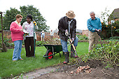 Group of older people gardening in a garden. MR