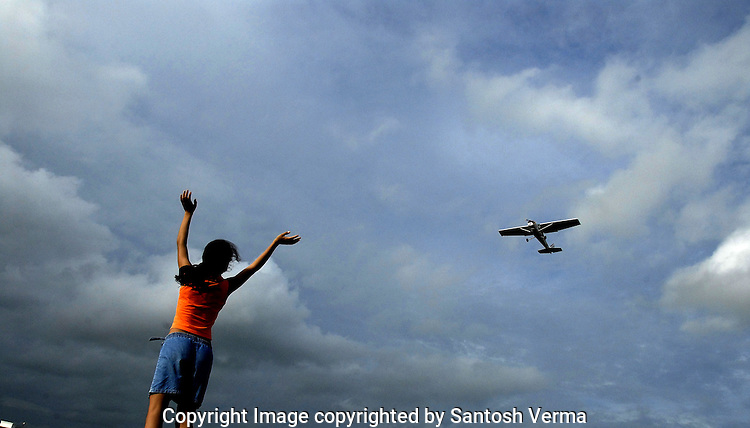 A young girl waves excitedly as a training aircraft passes over her at a Pilot's training Academy in Maharastra, India. Photograph  © Santosh Verma