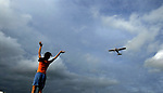 A young girl waves excitedly as a training aircraft passes over her at a Pilot's training Academy in Maharastra, India. Photograph  &copy; Santosh Verma