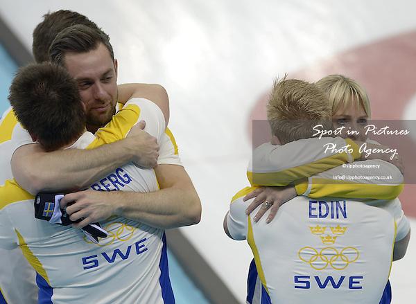 The Swedish team celebrate. (l to r)  Fredrik Lindberg (SWE) hugs Sebastian Kraupp (SWE, vice skip) and Niklas Edin (SWE, skip) hugs  Swedish coach Eva Lund. Mens curling - Bronze medal match - SWE v CHN - Ice Cube Curling Centre - Olympic Park - PHOTO: Mandatory by-line: Garry Bowden/SIPPA/Pinnacle - Photo Agency UK Tel: +44(0)1363 881025 - Mobile:0797 1270 681 - VAT Reg No: 768 6958 48 - 210214 - 2014 SOCHI WINTER OLYMPICS - Ice Cube Curling Centre, Sochi, Russia