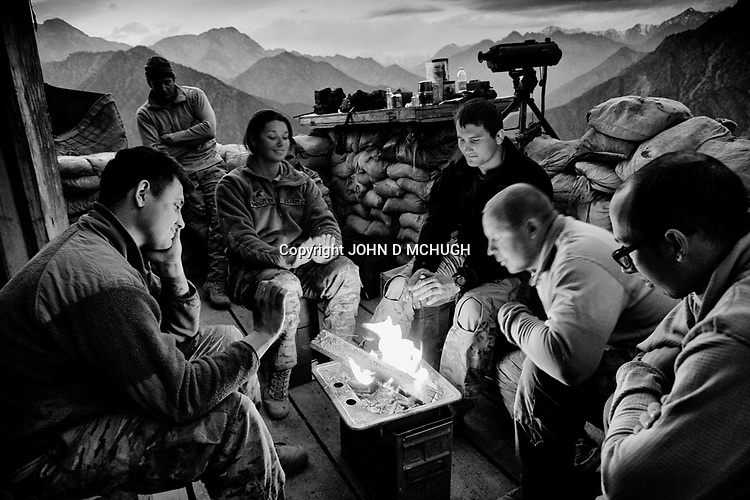 US soldiers sit around a fire for warmth at Observation Post Mace, near Gowerdesh in northern Kunar, 27 November 2011. (John D McHugh)