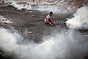 Local residents gather raw coal and process it in Borapahari in Jharia, Jharkhand, India. Coal fires rage just below the surface of the ground, making it too hot to walk with naked feet, noxious gases spew up from fissures, making the environment toxic. Residents who live above the furnace make $2 a day collecting small chunks of coal they sell to illegal middlemen. Photo: Sanjit Das