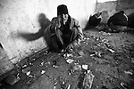 A man smoking opium objects to having his photo taken in the ruins of the former Soviet Cultural Center in Kabul, Afghanistan. More than 2,000 opium and heroin addicts gather each day to get high inside the derelict structure, which was almost completely destroyed during the 1992-1994 civil war. Feb. 2, 2009.