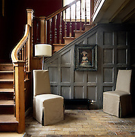 A pair of contemporary chairs in loose covers have been placed against the iron grey wood panelling beneath the staircase in this tiled hall