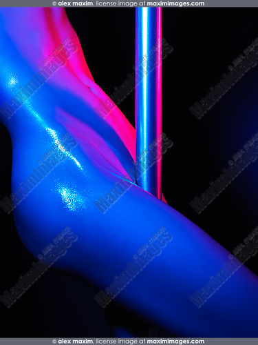 Closeup of shiny sexy nude body of a naked woman pole dancing in colorful blue red light