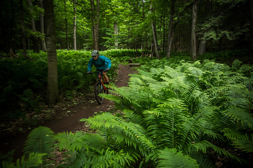 A female mountain biker rides the Noquemanon Trails Network's Gorgeous Trail along the Carp River in Marquette, Michigan.