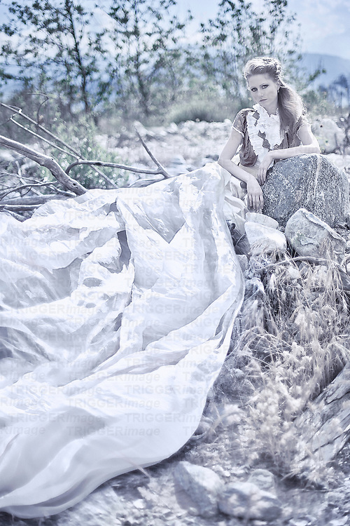 A young woman with long blonde hair wearing a long silk dress lounging outdoors alone in a rural landscape