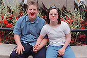 Teenage boy and girl with Downs Syndrome sitting together in park holding hands.  MR