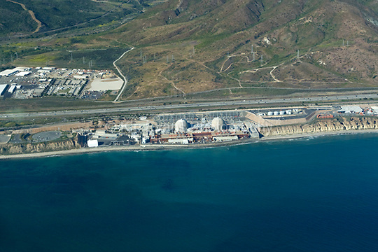 View of the San Onofre Nuclear Generating Station from the air looking northeast. The 84-acre (34 ha) site is in the northwestern corner of San Diego County, south of San Clemente, and surrounded by the San Onofre State Park. It provides nearly 20% of the electrical power to the residents of Southern California (wiki 2009).