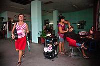 L'Avana negozio di parrucchiere privato, una signora esce dal negozio mentre la proprietaria pettina una cliente